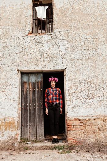 Portrait of man standing against door of house