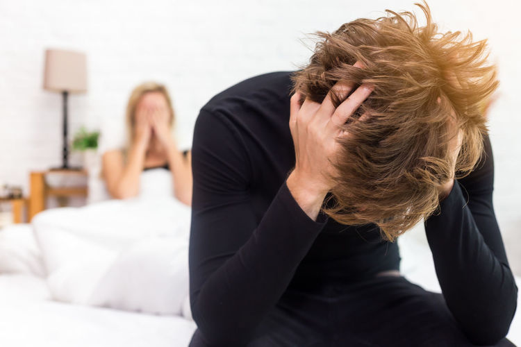 Tensed man with girlfriend sitting on bed at home