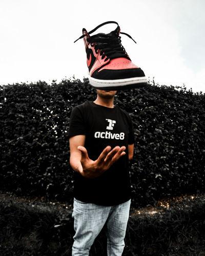 Man wearing hat standing against sky