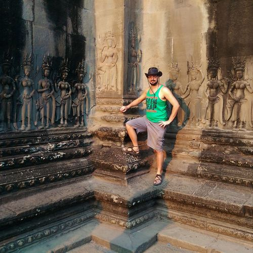 Full Length Portrait Of Young Man Standing By Temple At Angkor Wat