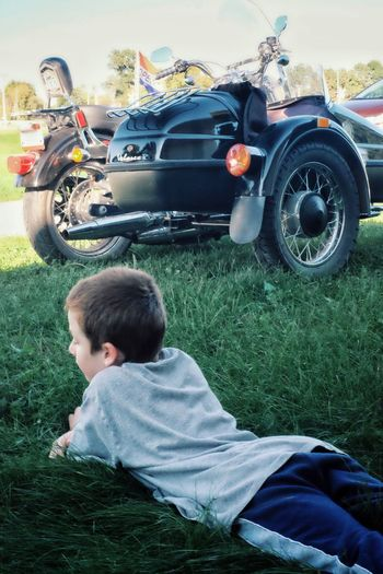 Boy Lying On Grassy Field By Parked Motor Scooter At Park
