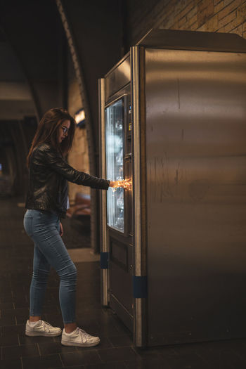 Side view of woman using vending machine
