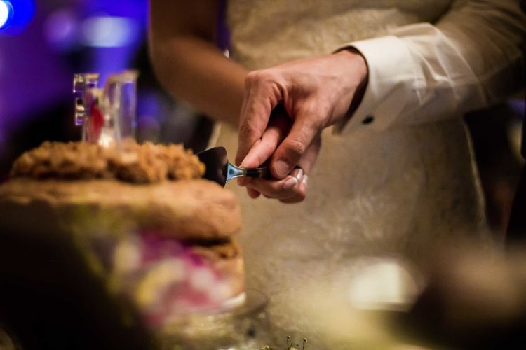 Midsection of wedding couple cutting cake during party