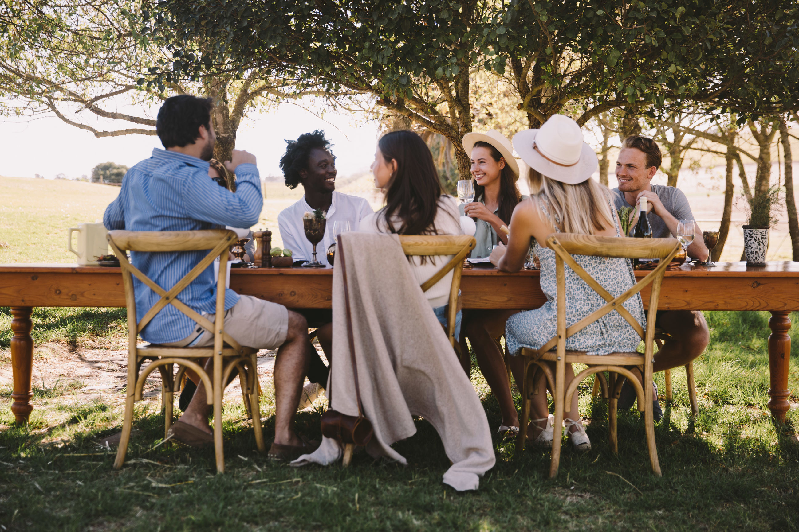 tree, sitting, plant, group of people, leisure activity, real people, seat, lifestyles, young adult, men, nature, casual clothing, people, togetherness, women, young men, land, adult, day, crowd, social gathering, outdoors