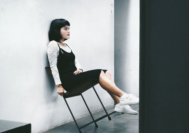 Young Woman Sitting On Chair Against Wall