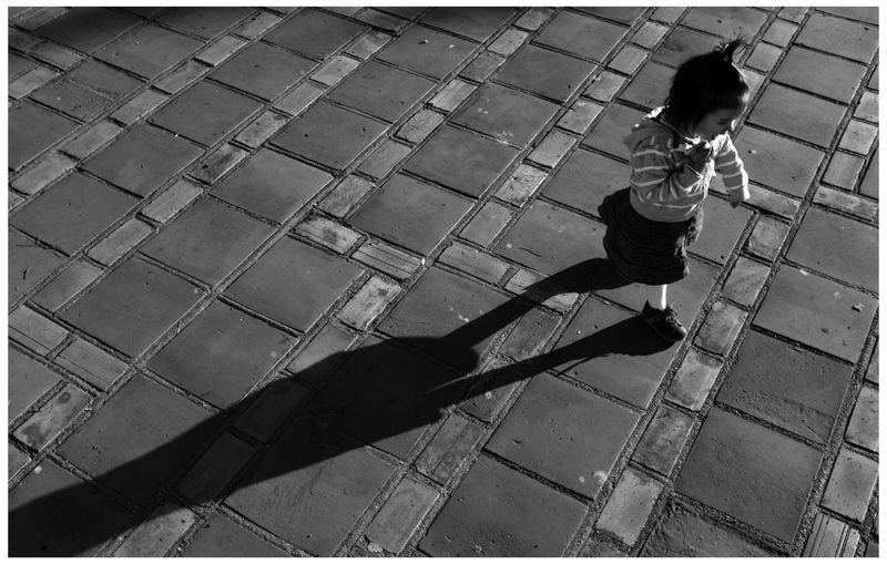 High angle view of boy playing on cobblestone