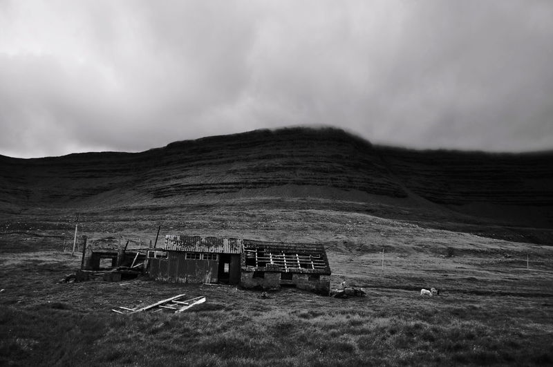 Broken hut on field with plateau in background against cloudy sky