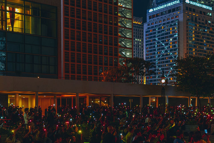 People protesting on street against illuminated buildings at night