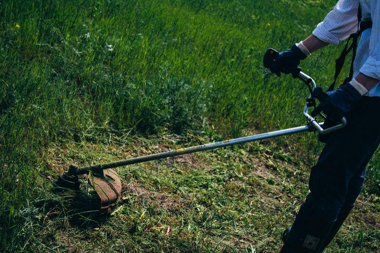 Cropped man mowing grassland