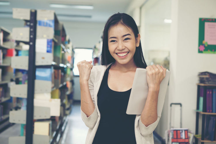 Smiling Young Woman With Clenched Fists In Library