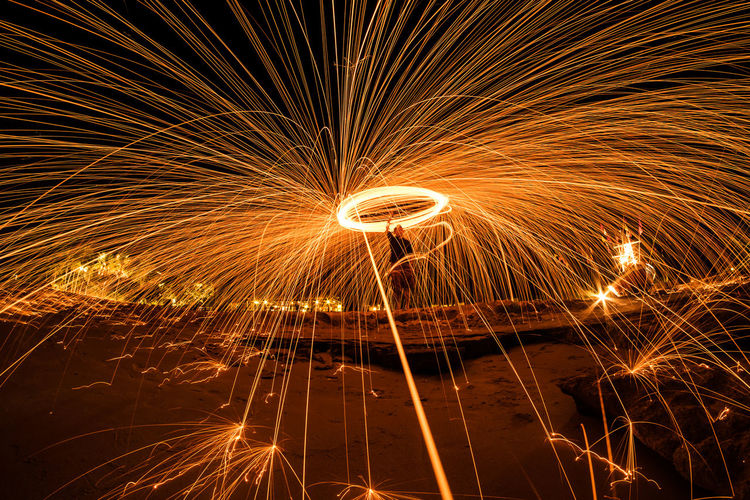 Mid Distance View Of Man Spinning Wire Wool At Night