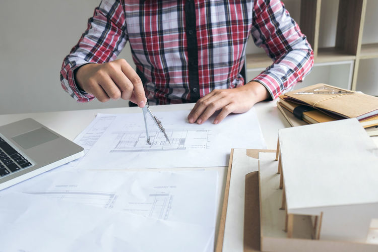 Midsection Of Architect Drawing Blueprint In Office