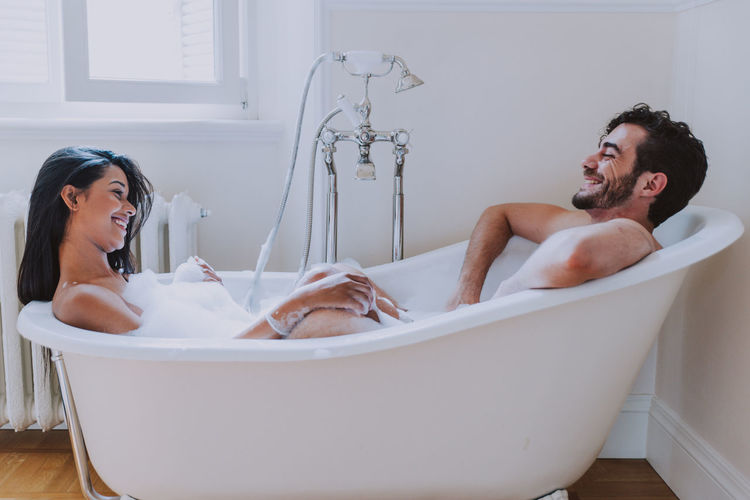 Side view of smiling couple sitting in bathtub