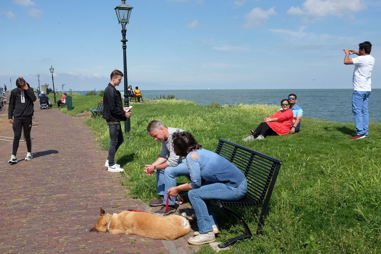 People with dog on sea shore against sky