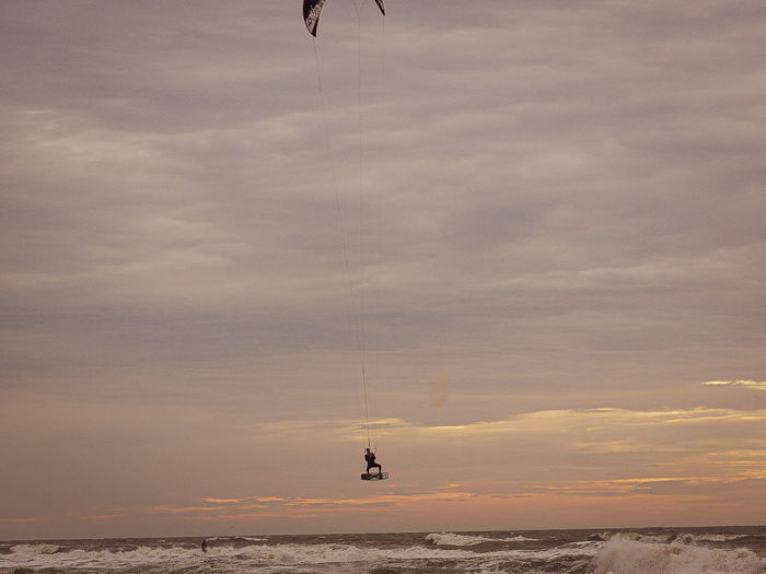 Person parasailing over sea against sky during sunset