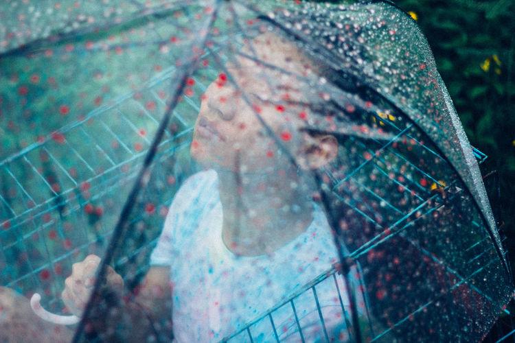 Man seen through wet umbrella during rainy season