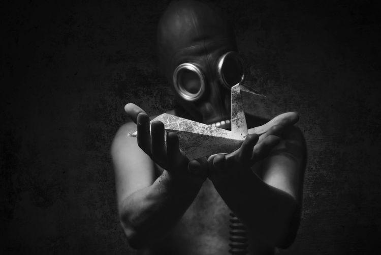 Man wearing gas mask in darkroom