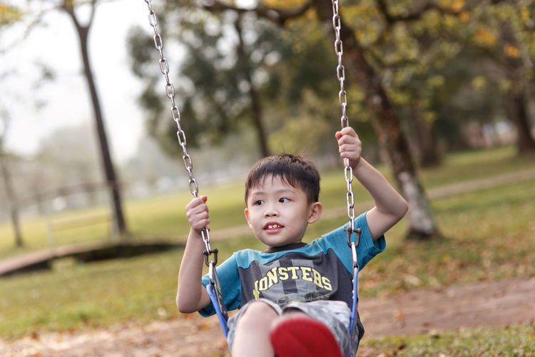 Boy playing on swing at park