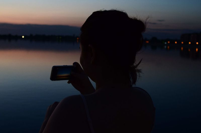 Silhouette woman photographing lake against sky during sunset
