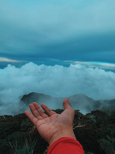 Cropped hand of man against cloudy sky