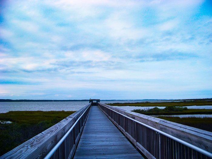 Bridge over calm sea against sky
