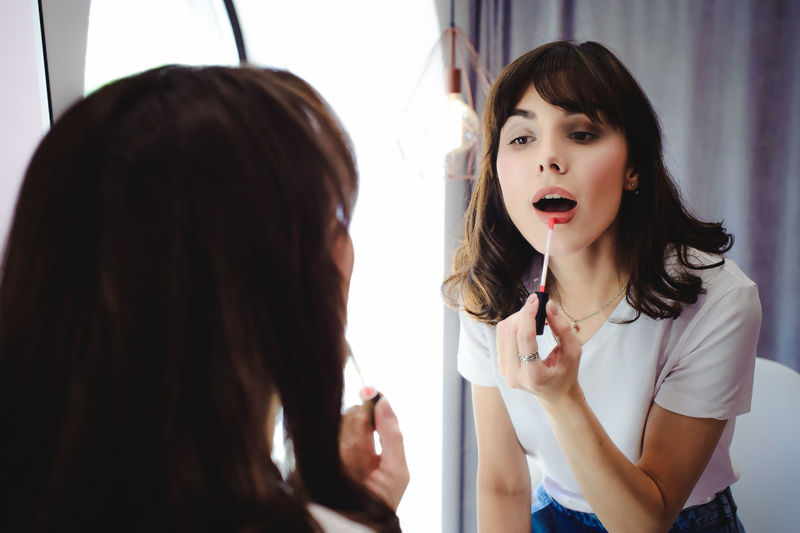 Portrait of a beautiful woman, dyes her lips lipstick pink, looking in the mirror Adult Beautiful Woman Beauty Brown Hair Day Friendship Human Hand Indoors  Lifestyles Make-up People Real People Two People Women Young Adult Young Women