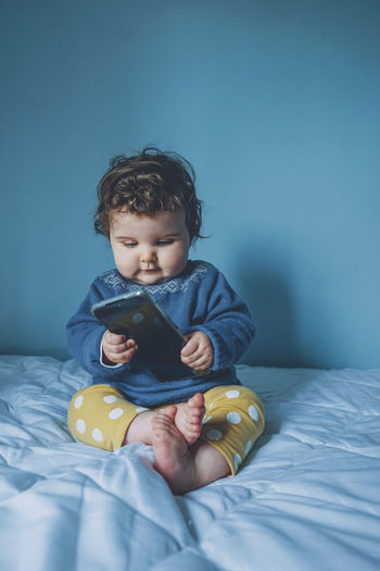 Cute boy using mobile phone while sitting on bed at home