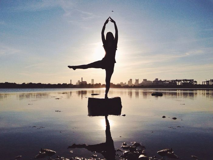 Silhouette woman doing yoga in sea against sky during sunset