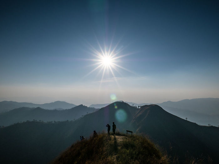 People on mountain against bright sun