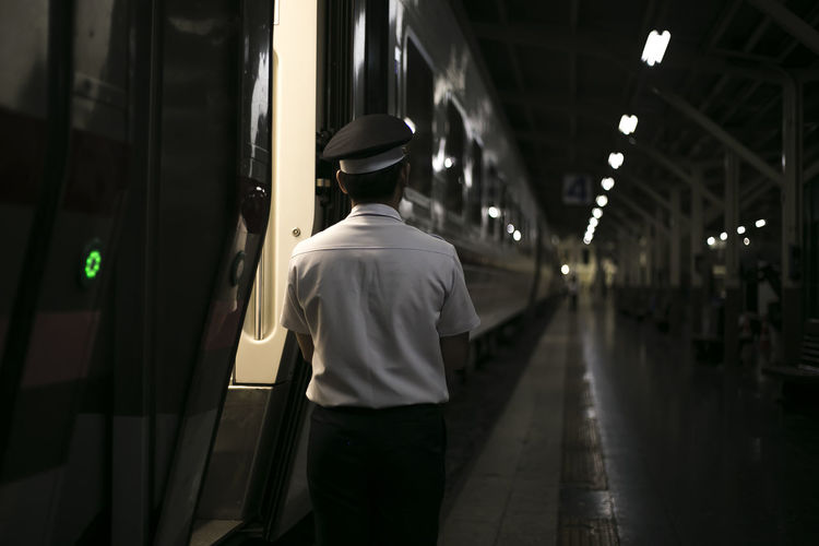 Adult Illuminated Indoors  Lifestyles Luggage Men Night One Person People Public Transportation Railroad Station Railroad Station Platform Real People Rear View Standing Train - Vehicle Transportation Walking