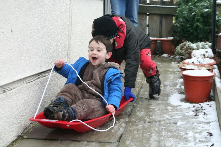 Two boys playing with sledge