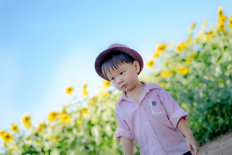 Low angle view of child standing on field against sky