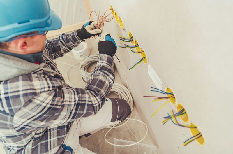 High angle view of electrician installing wires on wall