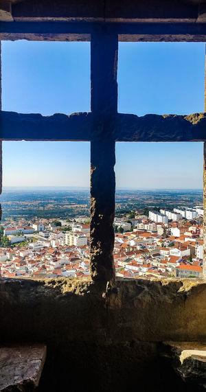 Cityscape by sea against sky seen through window