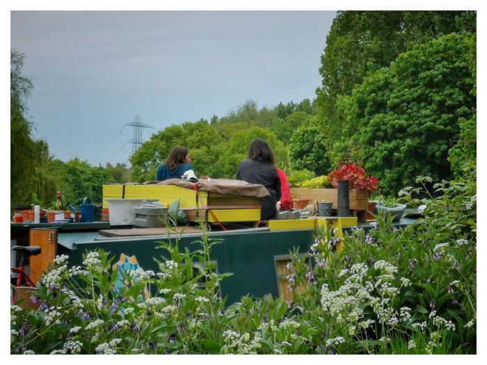 People sitting on boat against trees and plants