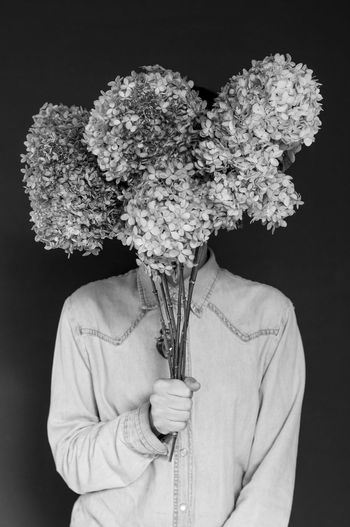 Man holding flowers against black background