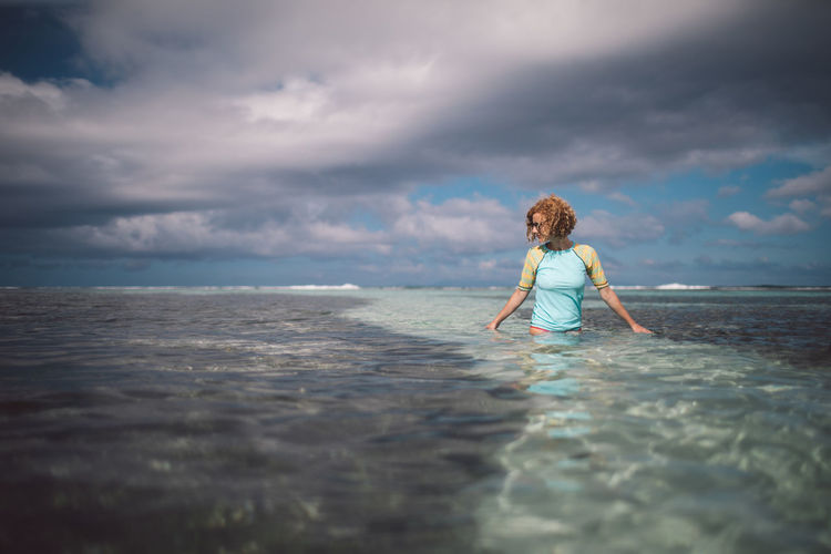 Woman standing in sea against cloudy sky