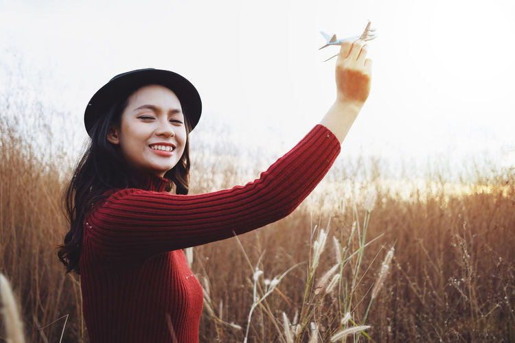 Side view of smiling young woman holding model airplane on land
