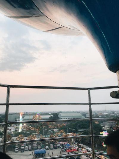 People in city against sky seen through window