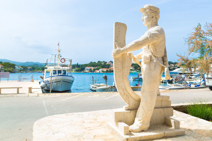 Statue of wooden boat craftsmanship in Lumbarda village, Croatia famous for traditional ship builders in Dalmatia Construction Croatia Honoring Korčula Respect Adriatic Sea Boat Building Croatian Holiday Croatian Summer Day Honor Korcula Island Korcula, Croatia Mode Of Transport Monument Moored No People Outdoors Sculpture Ship Building Sky Statue Sunlight Transportation Water