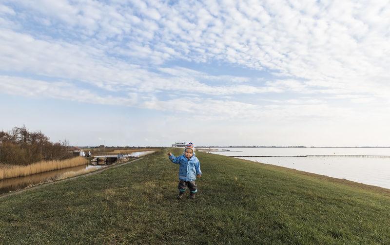 Girl Standing At Grassy Lakeshore Against Sky
