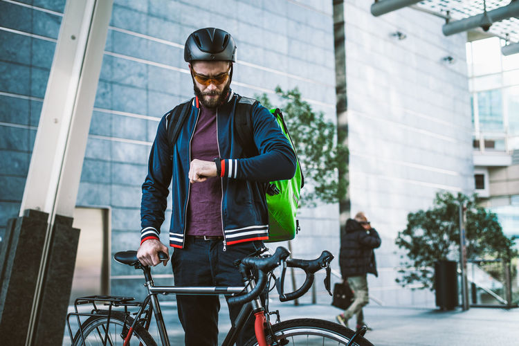 Man checking time while standing by bicycle outdoors