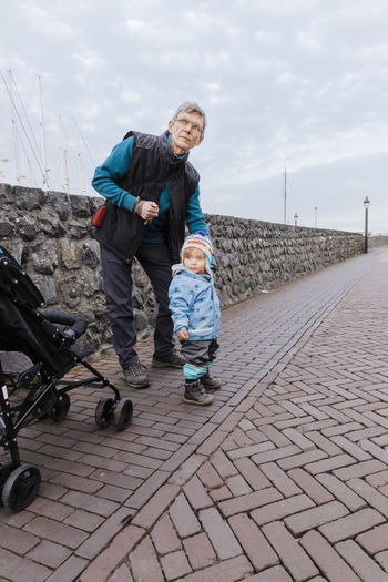 Man with toddler girl on sidewalk – Hindeloopen, Netherlands, Europe Man Mature Men Grandfather Protection Full Length Street Child Childhood Toddler  Holding Standing Outdoors Watching Granddaughter Family Serious Pedestrian Warm Clothing Two People Togetherness Traffic Looking Away Netherlands Wall Urban Lifestyle
