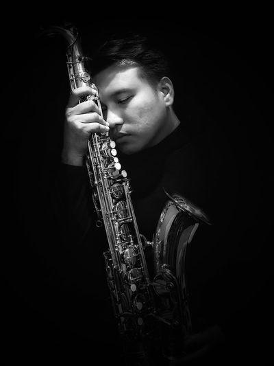 Man Holding Saxophone Against Black Background