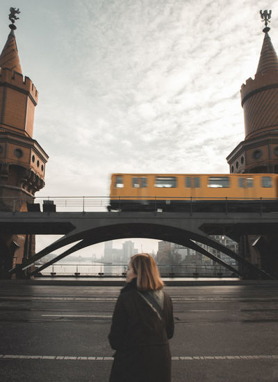 Rear view of woman against bridge with passing train