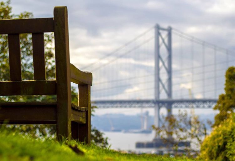 Wooden Chair On Field Against Forth Road Bridge