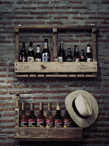 Beer Container Bottle Side By Side Drink Food And Drink Refreshment Alcohol Arrangement Large Group Of Objects In A Row Wine Bottle Shelf Bar - Drink Establishment Wood - Material Wall - Building Feature Indoors  Variation No People Still Life Choice