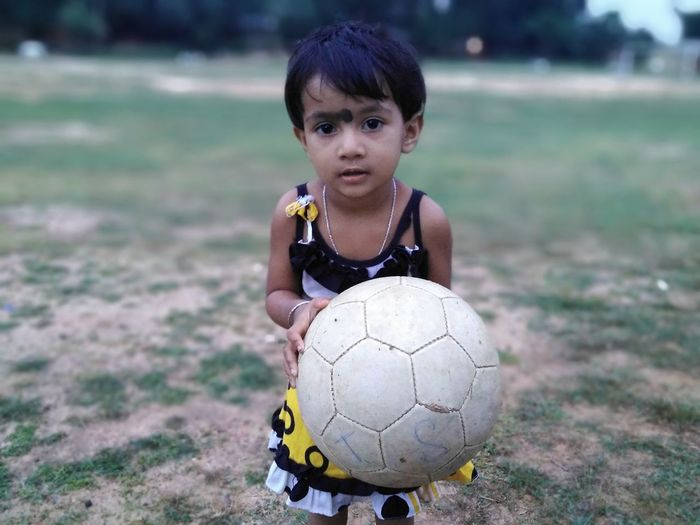 Portrait of girl holding ball on field