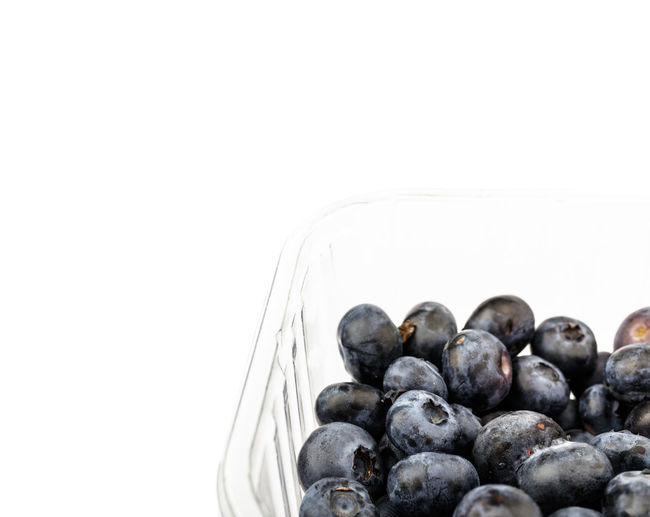 Close-up of blueberries in bowl against white background