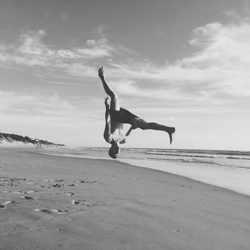 Young Man Jumping At Beach Against Sky